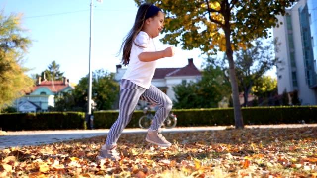 vidéos et rushes de fille de joyeux bambin bénéficiant d'automne dans un parc de la ville - vue latérale