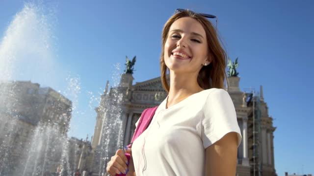 stockvideo's en b-roll-footage met vrolijke toeristische meisje permanent in de buurt van fontein - wit t shirt