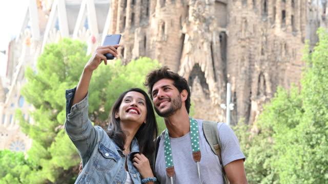Cheerful travelers taking selfie in front of Sagrada Familia