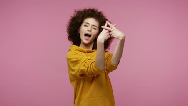 glad trendig flicka afro frisyr i hoodie visar hashtag gest, märkning viral webbinnehåll, berömd idé - tema bildbanksvideor och videomaterial från bakom kulisserna