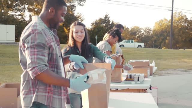 yemek sürüşü sırasında birlikte çalışan neşeli gönüllüler - giving tuesday stok videoları ve detay görüntü çekimi