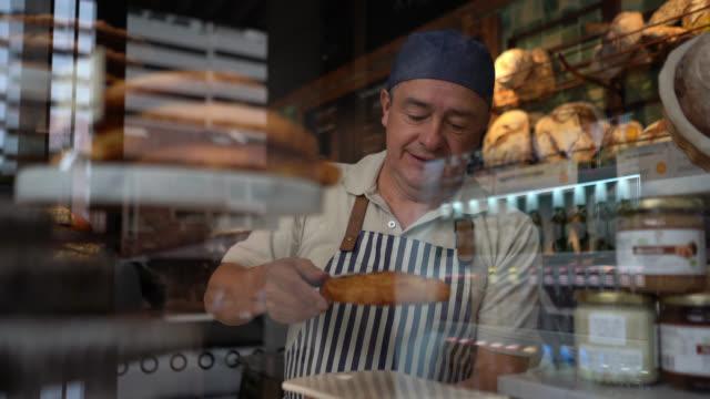 vidéos et rushes de serveur gai saisissant une casse-croûte sucrée de pâtisserie et la plaçant sur l'assiette à une boulangerie - boulanger