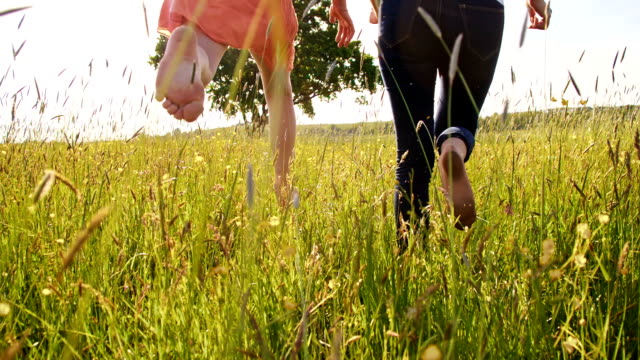SLO MO Cheerful woman and girl running barefoot in grass video