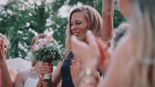 Cheerful woman catching flower bouquet in wedding
