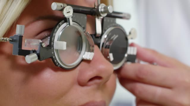 Cheerful Woman Checking Vision at Optometrist Extreme close up shot with tilt up of cheerful blond woman wearing trial frame nodding as unrecognizable optometrist changing lenses and asking questions eye chart stock videos & royalty-free footage