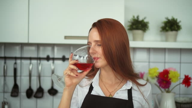 cheerful woman drinking wine in domestic kitchen. redhead person closeup. - уход за фигурой стоковые видео и кадры b-roll