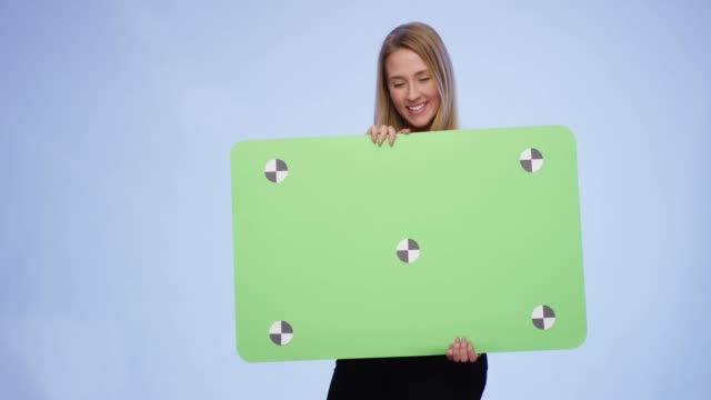 cheerful woman holding oversized blank card on blue background - business card stock videos & royalty-free footage