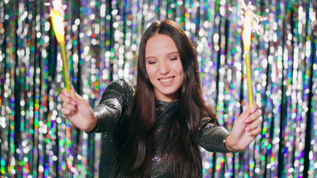 Cheerful woman holding sparklers at the party. Teenage girl enjoying new years eve with fireworks. Celebration, bachelorette party, birthday, winter holidays. There is a shiny curtains background