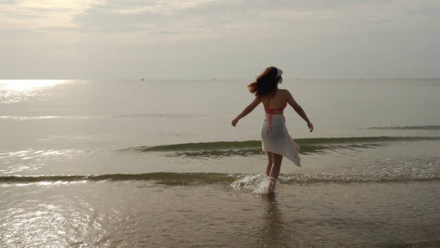 vidéos et rushes de femme gaie dans le bikini appréciant sur la plage de mer avec la lumière du soleil - bras humain