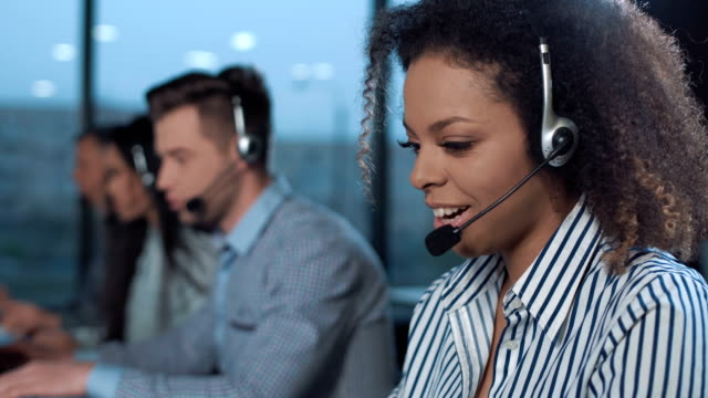 stets gut gelaunte frau im call-center - callcenter stock-videos und b-roll-filmmaterial