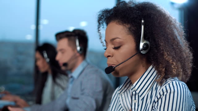 Cheerful woman in call center Woman talking to the client with headset and smiling while looking at camera. prop stock videos & royalty-free footage