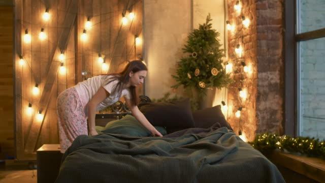 neşeli kadın pijama yatak sabah yapma - yapmak stok videoları ve detay görüntü çekimi