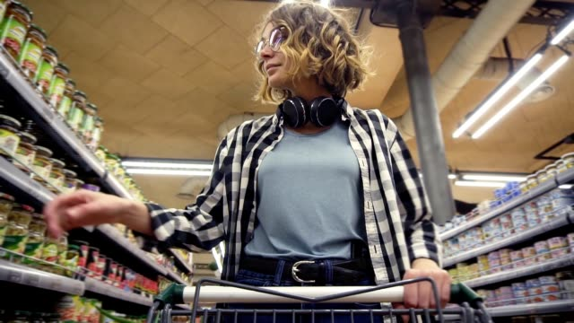 Cheerful woman in plaid shirt and headphones on neck is walking in grocery store steering shopping trolley with food inside it and looking around at shelves with products, take a jar and put it to a cart. Low angle footage from the cart video