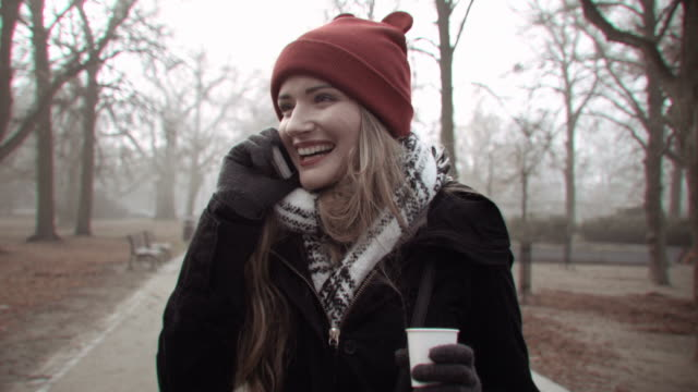 Cheerful woman in red hat holding coffee and talking on the phone, outdoors. video