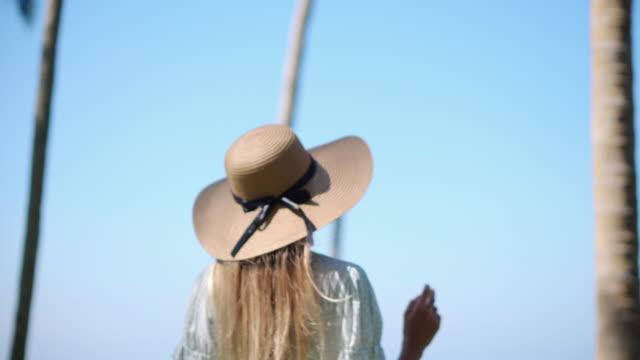 vídeos y material grabado en eventos de stock de mujer alegre con sombrero de sol caminando al aire libre - disquete