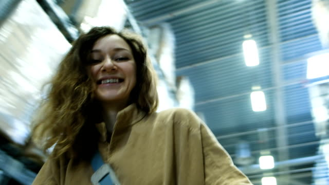 Cheerful woman is spinning with a cart in the warehouse of a shopping center video