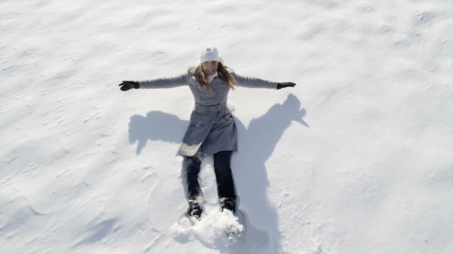 SLOW MOTION: Cheerful woman making angels in fresh snow video