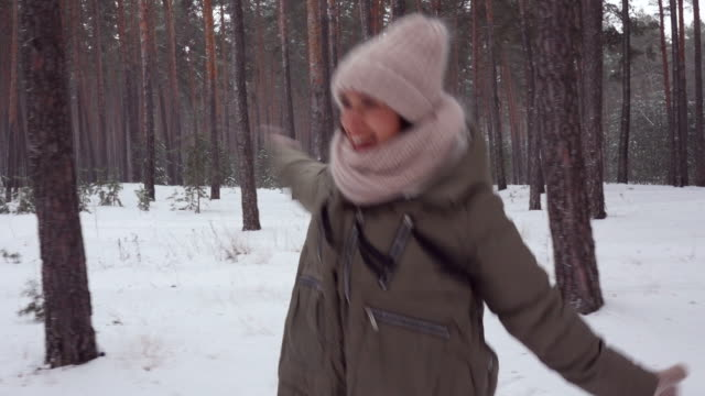 Cheerful woman merrily jumping in woods, dolly shot video