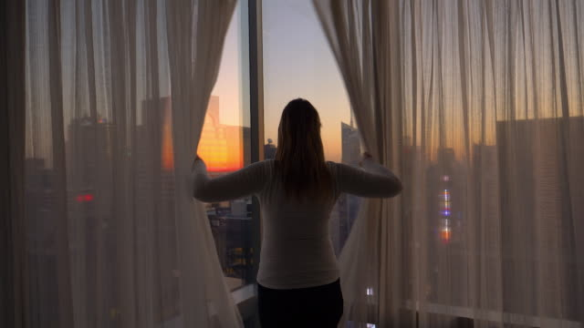CLOSE UP: Cheerful woman opens the curtains and looks at the city at sunset. video
