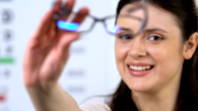 Cheerful woman proposing eyeglasses, patient recommendation, vision support Cheerful woman proposing eyeglasses, patient recommendation, vision support eye chart stock videos & royalty-free footage