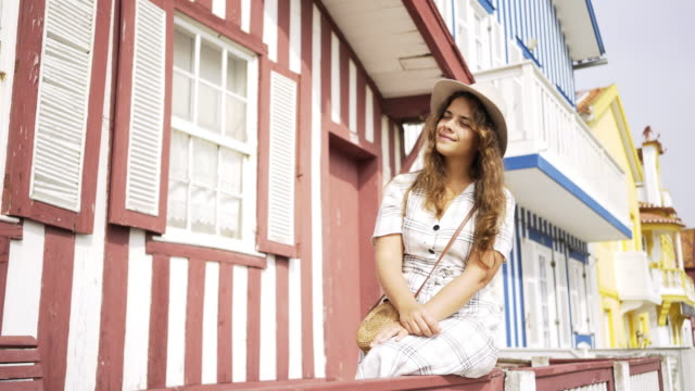vídeos de stock e filmes b-roll de cheerful woman sitting near striped house - aveiro