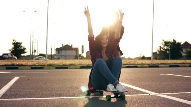 Cheerful woman sitting on a longboard and raising her hands up happily while her friend is pushing her behind during sunset. Lens flare. Slowmotion shot video