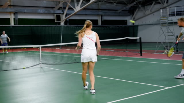 Cheerful woman standing against tennis team on court video