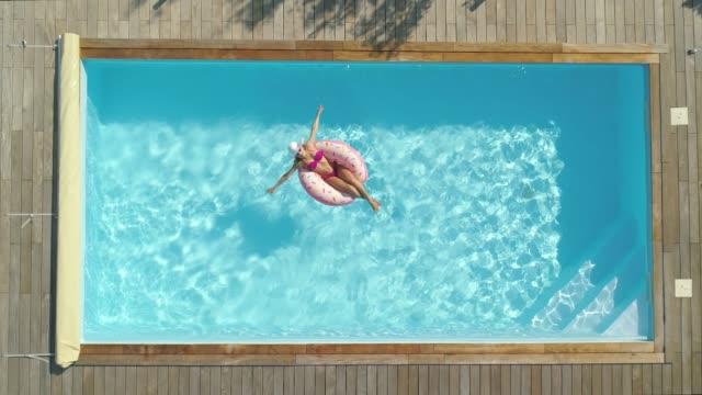 vídeos de stock, filmes e b-roll de antena, de cima para baixo: mulher alegre banhos de sol enquanto relaxa na piscina quintal. - inflável