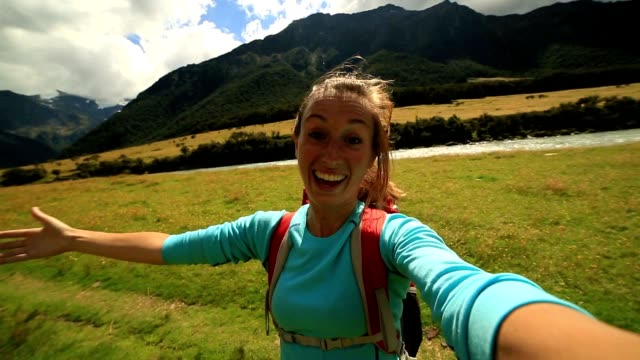 Cheerful woman takes a self portrait in mountain valley, video