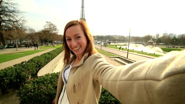 vídeos de stock, filmes e b-roll de alegre mulher segura selfie em paris com a torre eiffel - moda parisiense