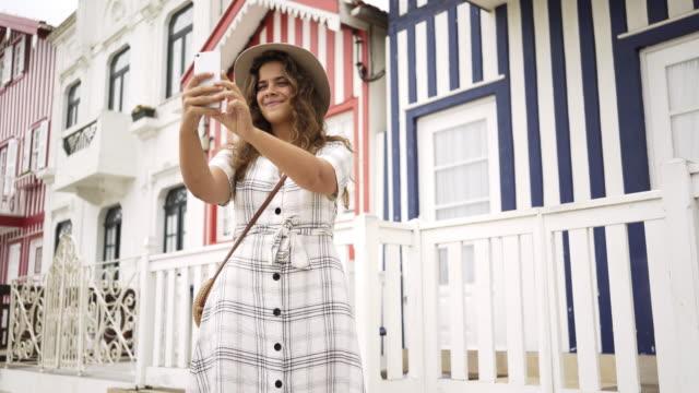 vídeos de stock e filmes b-roll de cheerful woman taking selfie near colorful houses - aveiro