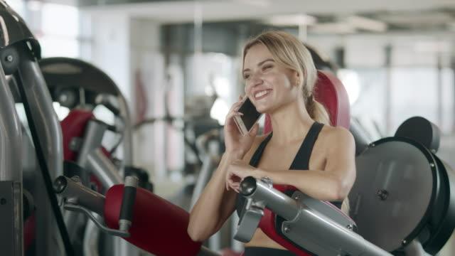 stockvideo's en b-roll-footage met vrolijke vrouw pratende mobiele telefoon op fitness trainings machine in sport gym. - call center
