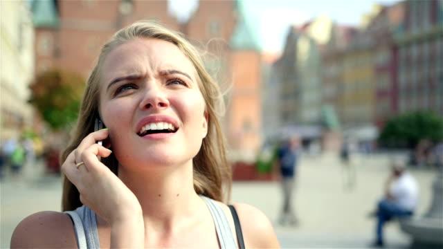 vídeos y material grabado en eventos de stock de alegre mujer hablando por teléfono celular en la ciudad. - animal joven