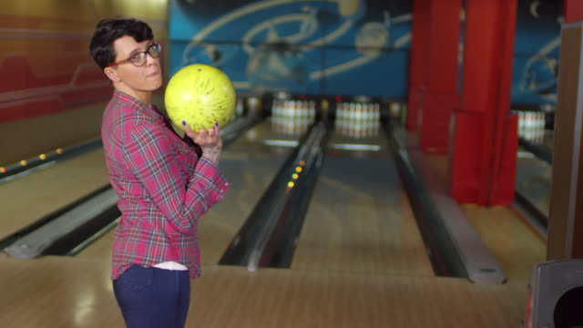 Cheerful Woman Throwing Bowling Ball and Missing