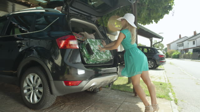 LENS FLARE: Cheerful woman tries to fit all her baggage in the boot of her SUV. LENS FLARE: Cheerful woman tries to fit all her baggage in the boot of her SUV. Caucasian girl having problems squeezing all suitcases in one car. Goofy female tourist overpacked for her vacation. stuffed stock videos & royalty-free footage