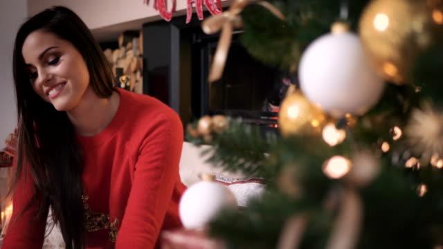 gladlynt kvinna uppackning presentförpackning på julgran - christmas presents bildbanksvideor och videomaterial från bakom kulisserna