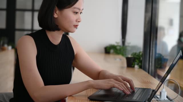 ノートパソコンを使用して陽気な女性は、カメラに向かって回転し、笑顔 - 美人点の映像素材/bロール