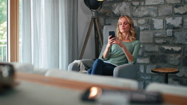 Cheerful woman using mobile phone at home