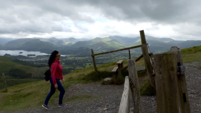 Cheerful woman walking to the gate on the hill video