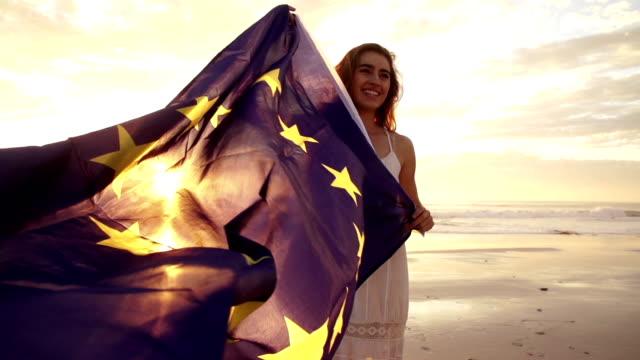 Cheerful woman waving european flag with sun flaring video