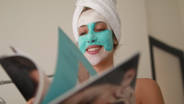 Cheerful woman with a beauty mask reading a magazine at a spa