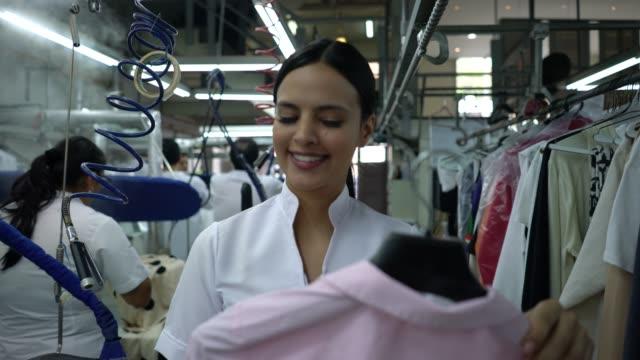 工業洗濯サービスで働いている陽気な女性がシャツを掛けるためにレールを探して歩いている - 楽しい 洗濯点の映像素材/bロール