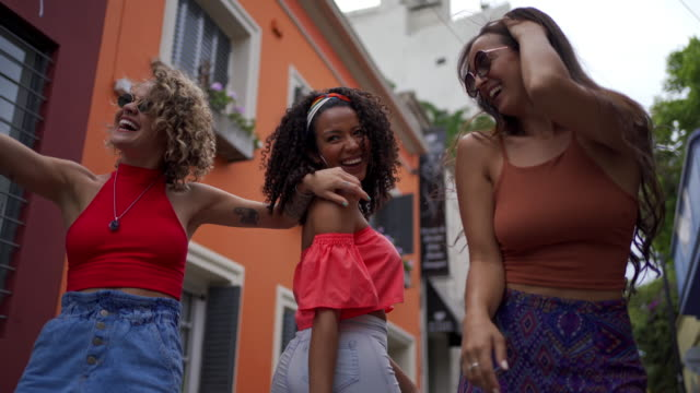 cheerful women dancing while walking on the street on a sunny day - amicizia tra donne video stock e b–roll