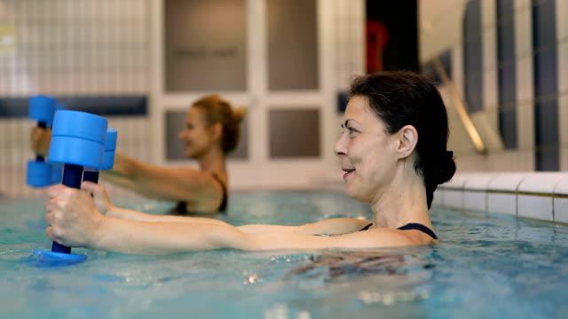 cheerful women exercising with dumbbells in pool - 40 49 lat filmów i materiałów b-roll