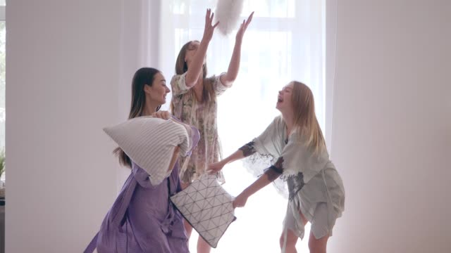 cheerful women friends jump and fight with pillows on the bed during pajama party in slow motion - bielizna nocna filmów i materiałów b-roll