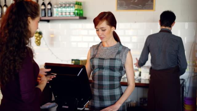 kahvehane neşeli işçileri ödemeler banka kartlarını kullanarak smartphone ile terminal ve satış paket servisi olan restoran içecekler gençlere alarak tebrik, müşterilerdir. - sipariş vermek stok videoları ve detay görüntü çekimi