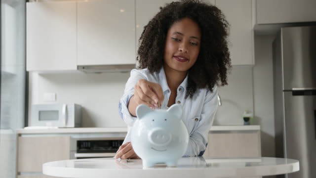 Cheerful young afro woman at home inserting coins into piggy bank Cheerful young afro woman at home inserting coins into piggy bank - Lifestyles piggy bank stock videos & royalty-free footage