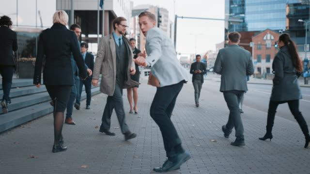 glad ung affärsman i en grå kavaj är aktivt dansar på en stadsgata. office manager flyttar genom upptagen kontorsfolk som pendlar till jobbet. downtown med skyskrapor i bakgrunden. - blazer bildbanksvideor och videomaterial från bakom kulisserna