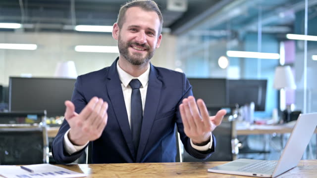 Cheerful Young Businessman Pointing finger and Inviting