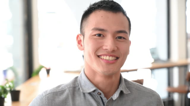 Cheerful young businessman with toothy smile turning head